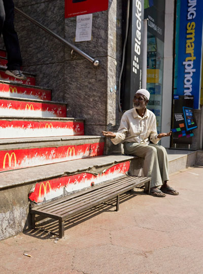Indian man begging outside MacDonalds in Bangalore, India