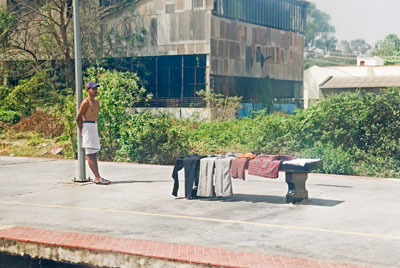 Indian man drying clothes after washing himself on a train track