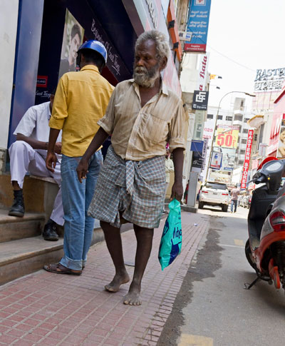 A old man walking through Commercial Street in Bangalore, India
