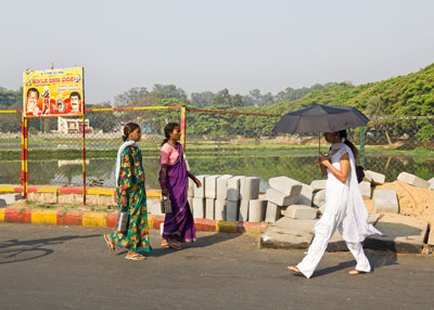 Indian Ladies walking in the midday sun past Ulsoor lake in Bangalore