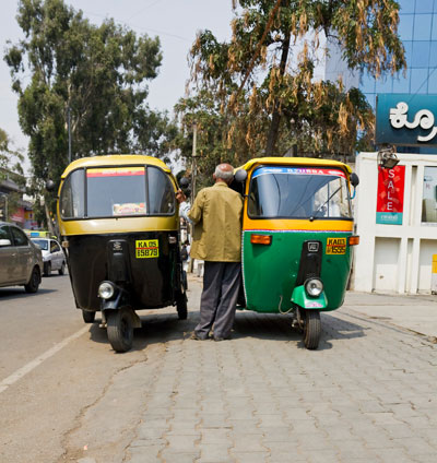 Two tut tut drivers chatting in Bangalore, India